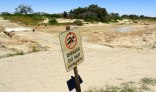 Danger sign on nearly empty Diamantina River